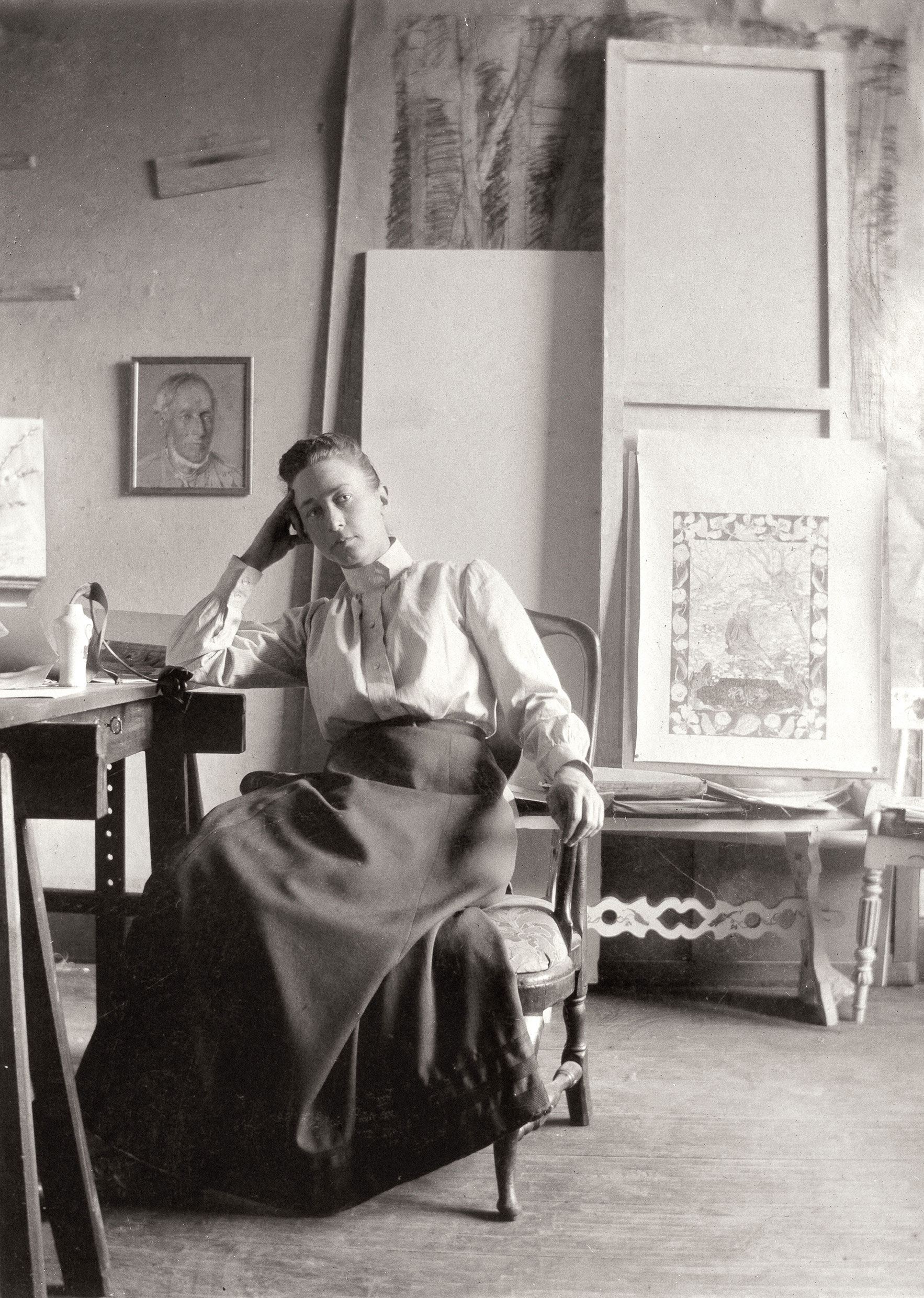 The artist Hilma af Klint sitting in her studio, wearing a long skirt and high-collared blouse.