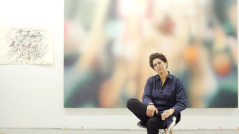Artist Julie Mehretu sits on a chair in a studio