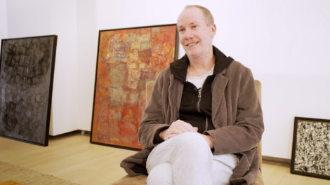 Artist Richard Prince sits on a chair in front of paintings in the Guggenheim Museum.